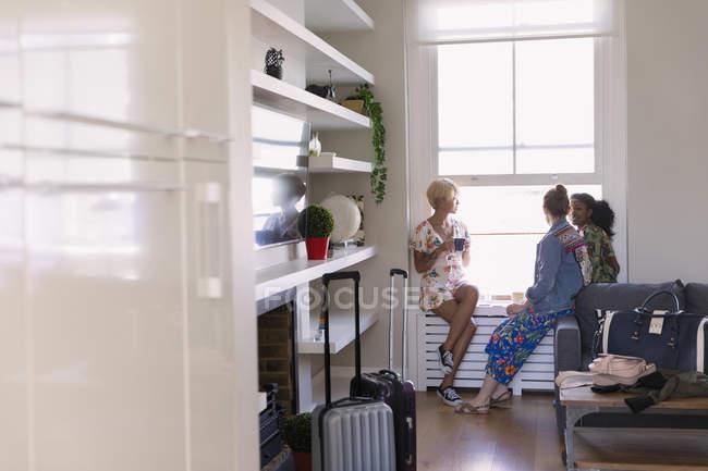 Amici delle giovani donne ne in casa affitto finestra — Foto stock