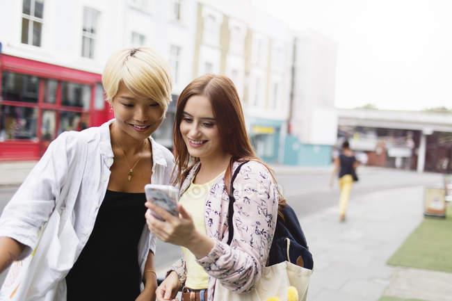 Jeunes femmes amis textos avec téléphone intelligent sur la rue urbaine — Photo de stock