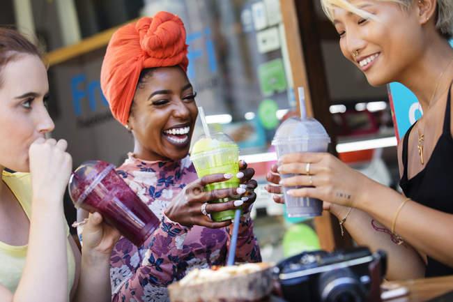 Junge Freundinnen trinken Smoothies im Straßencafé — Stockfoto