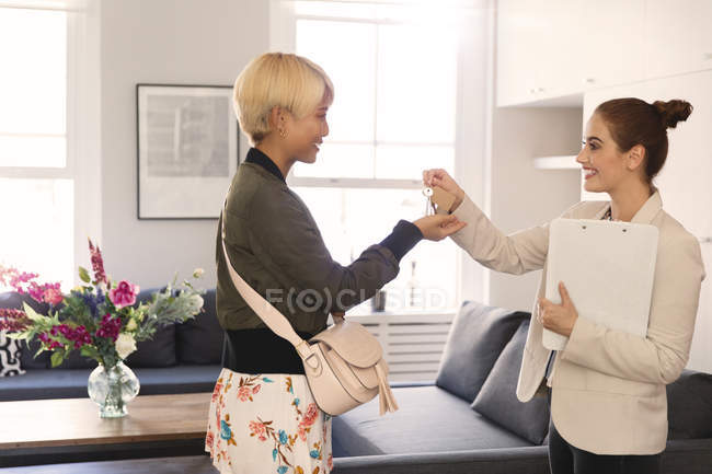 Real estate agent giving apartment keys to young woman — Stock Photo