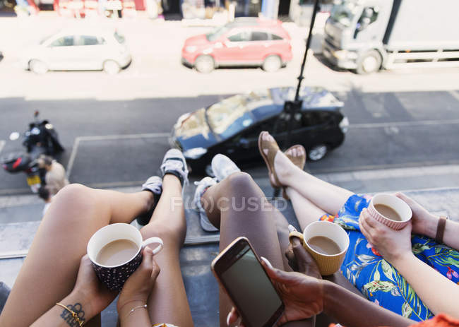Women friends drinking coffee, dangling legs out urban apartment window — Stock Photo