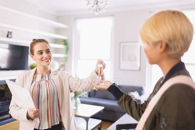 Real estate agent giving keys to woman in apartment — Stock Photo