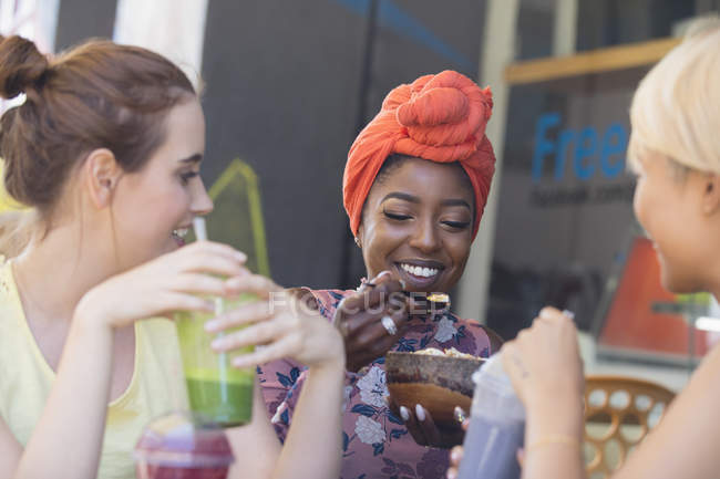Junge Frauen Freunde Smoothies trinken und Essen im Straßencafé — Stockfoto