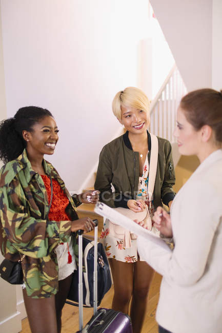 Real estate agent talking to young women with suitcases in house rental — Stock Photo