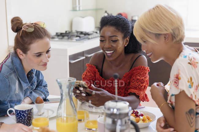 Amis de jeunes femmes appréciant leur petit-déjeuner, en utilisant le téléphone intelligent en cuisine — Photo de stock