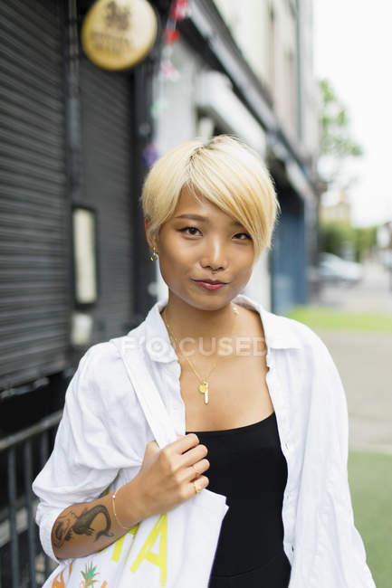 Portrait confident young woman on urban sidewalk — Stock Photo