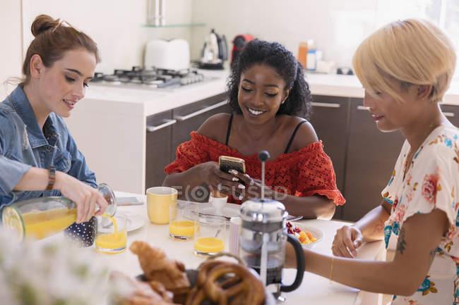 Amigos de mulheres jovens desfrutar de pequeno-almoço na mesa da cozinha — Fotografia de Stock
