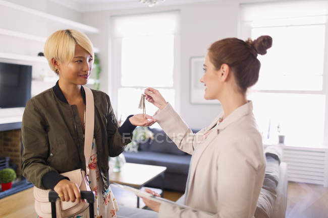 Real estate agent giving house rental keys to young woman — Stock Photo