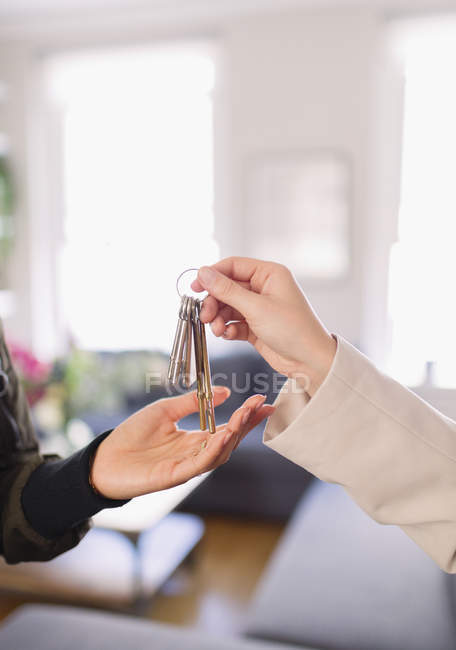 Close up real estate agent giving house keys to woman — Stock Photo