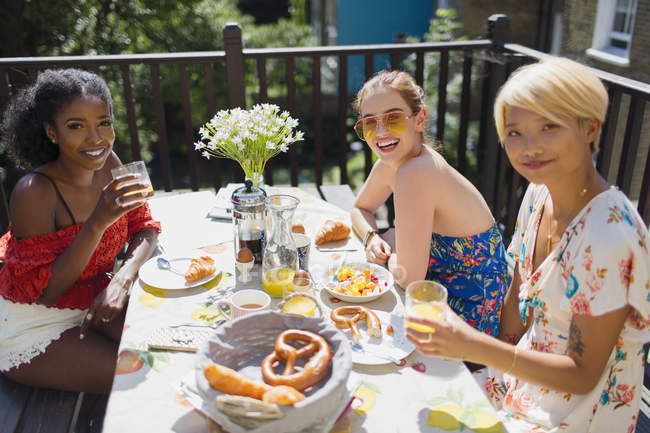 Portrait smiling young women enjoying brunch on sunny balcony — Stock Photo