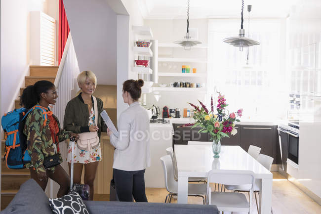 Real estate agent greeting young women friends arriving at house rental — Stock Photo