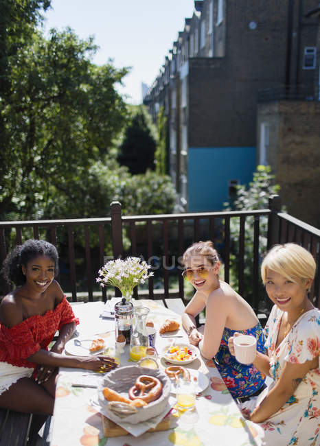 Portrait smiling young women friends enjoying brunch on sunny apartment balcony — Stock Photo