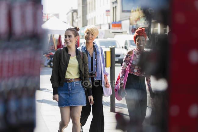 Amis de jeunes femmes marchant sur le trottoir urbain — Photo de stock