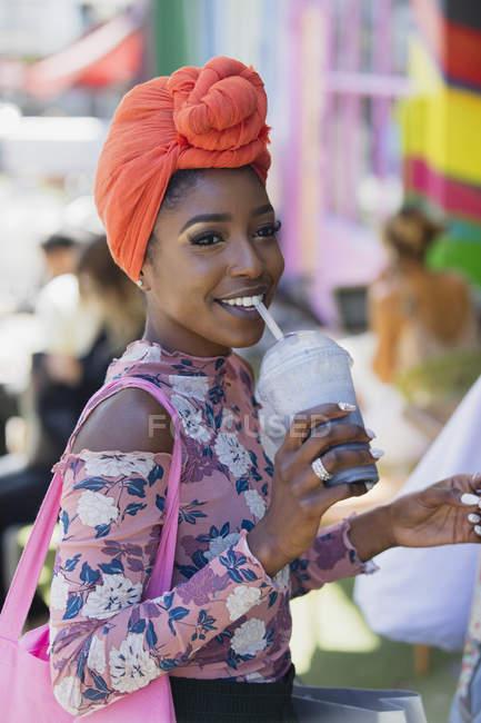 Lächelnde junge Frau mit Kopftuch trinkt Smoothie — Stockfoto