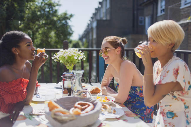 Young women friends enjoying brunch on sunny apartment balcony — Stock Photo
