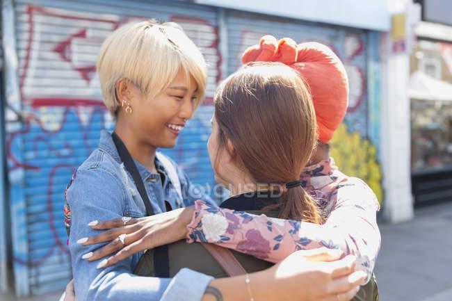 Happy young women friends hugging on urban sidewalk — Stock Photo