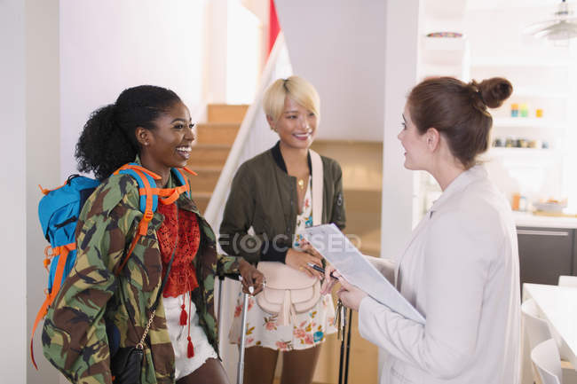 Real estate agent greeting young women friends at house rental — Stock Photo