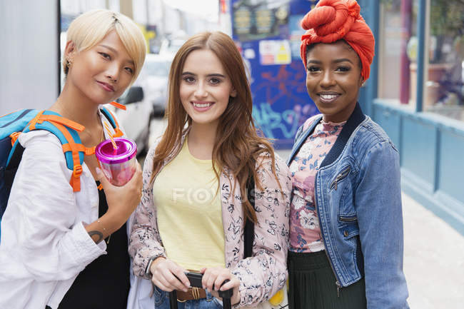 Portrait young women friends on urban sidewalk — Stock Photo