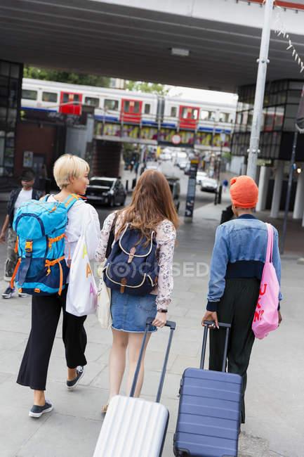 Junge Freundinnen mit Koffern vor S-Bahnhof — Stockfoto