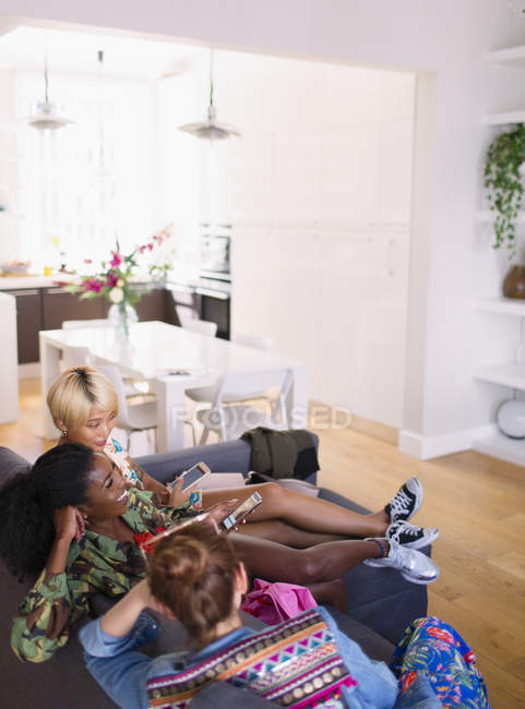 Young women friends hanging out, using smart phones on apartment sofa — Stock Photo
