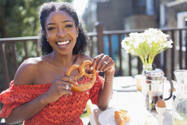 Portrait smiling, confident young woman with pretzel enjoying breakfast on sunny balcony — Fotografia de Stock
