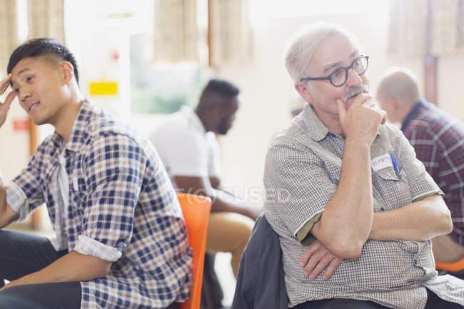 Hommes parlant et écoutant en thérapie de groupe dans un centre communautaire — Photo de stock