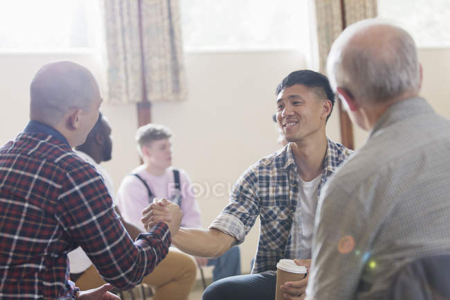 Men shaking hands in group therapy in community center — Stock Photo