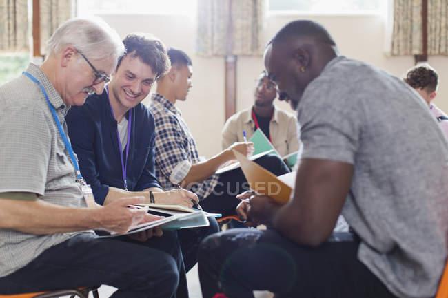 Мужчины, читающие документы в групповой терапии в общественном центре — стоковое фото