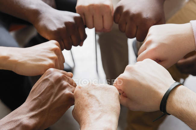 Men joining fists in circle — Stock Photo
