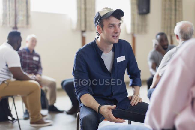 Young man talking in group therapy in community center — Stock Photo