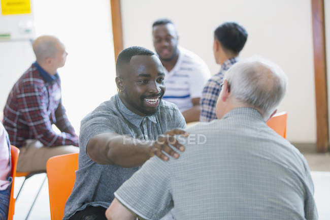 Smiling, happy man talking, comforting man in group therapy — Stock Photo
