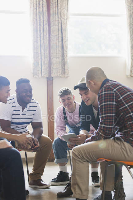 Men with digital tablet talking in group therapy circle — Stock Photo