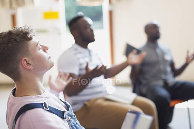 Serene man praying with arms outstretched in prayer group — Stock Photo