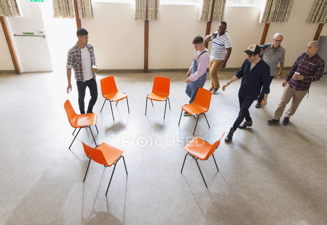 Men arriving at group therapy, sitting in circle in community center — Stock Photo