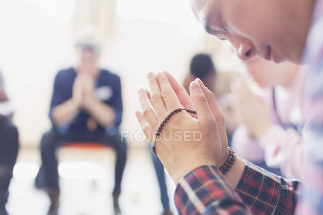 Man praying with prayer beads in prayer group — Stock Photo