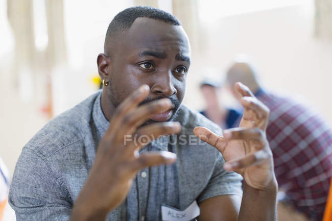 Serious young man talking, gesturing in group therapy — Stock Photo