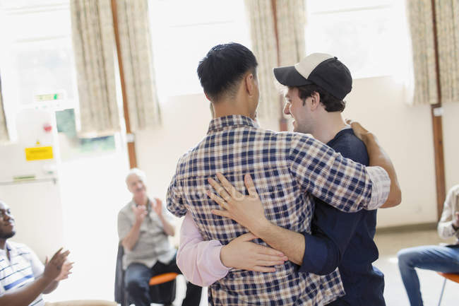 Uomini che si abbracciano in terapia di gruppo — Foto stock