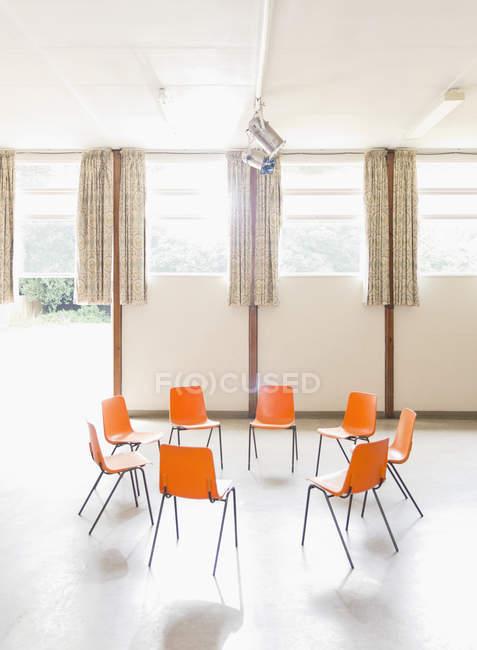 Laranja cadeiras dispostas em círculo no centro comunitário — Fotografia de Stock