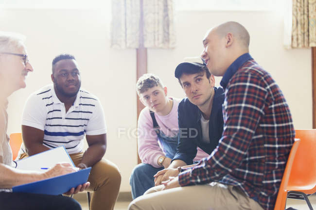 Attentive men talking and listening in group therapy — Stock Photo