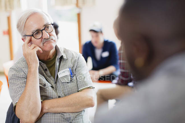 Attentive senior man listening in group therapy — Stock Photo
