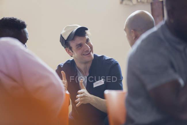 Uomo sorridente che comunica in terapia di gruppo — Foto stock