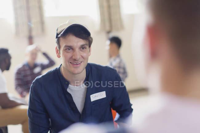 Uomo sorridente ascolto in terapia di gruppo — Foto stock