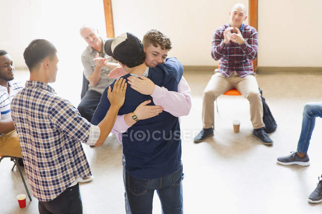 Men hugging and clapping in group therapy — Stock Photo