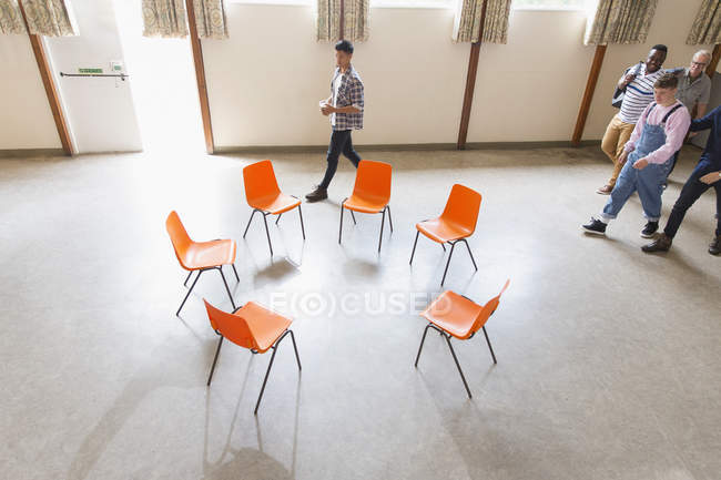 Men arriving, approaching chairs in circle in community center — Stock Photo