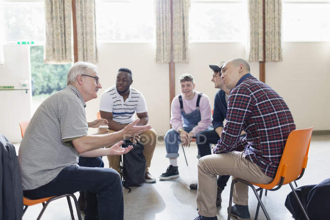 Men talking and listening in group therapy — Stock Photo