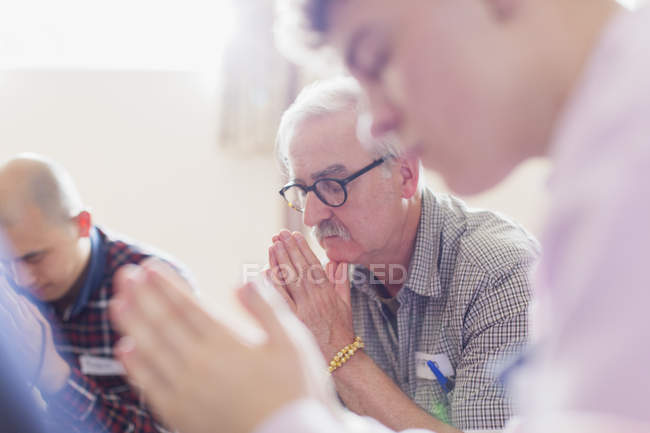 Men praying in prayer group — Stock Photo