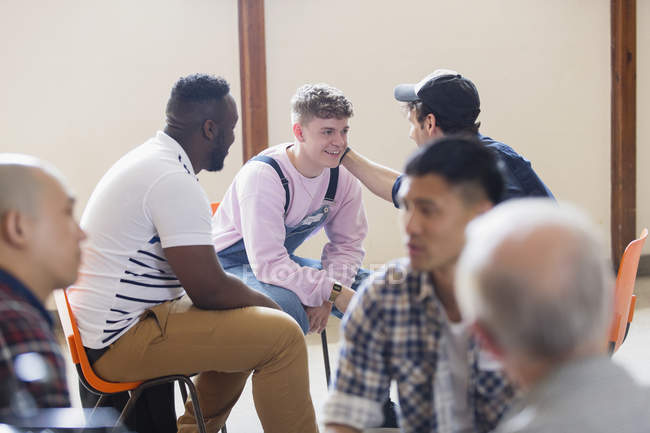 Men talking, comforting in group therapy — Stock Photo