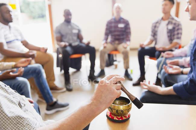 Людина за допомогою співочої чаші в медитації Група — стокове фото