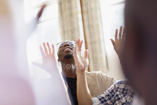 Smiling man with arms raised praying in prayer group — Stock Photo