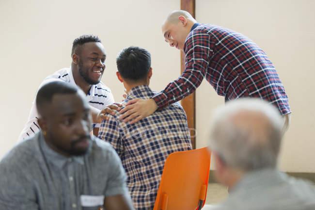 Мужчины разговаривают, утешают в групповой терапии — стоковое фото